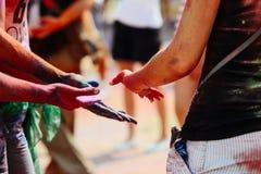 Mains des hippies heureux avec la poudre colorée au fest de holi, festi Photos stock