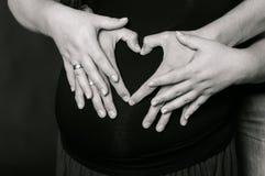 Mains des hommes et des femmes sur le ventre enceinte Image libre de droits