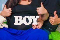 Mains des hommes et des femmes sur le ventre enceinte Images libres de droits