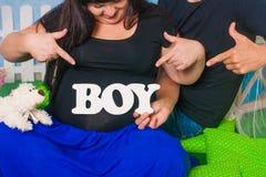 Mains des hommes et des femmes sur le ventre enceinte Photos libres de droits
