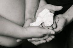 Mains des hommes et des femmes sur le ventre enceinte avec des chaussettes Photo stock