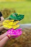 Mains des jeunes couvertes dans des couleurs de Holi d'isolement Photos stock