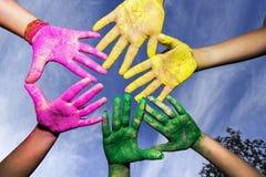 Mains des jeunes couvertes dans des couleurs de Holi sous le ciel bleu Photos stock