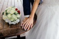 Mains des jeunes mariés avec des anneaux et bouquet des roses blanches et des orchidées sur la table Photos stock