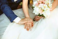 Mains des jeunes mariés avec des anneaux épousant le bouquet Photos stock