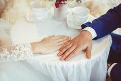 Mains des jeunes mariés avec des anneaux Photographie stock libre de droits