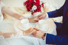 Mains des jeunes mariés avec des anneaux Image libre de droits