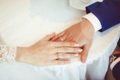 Mains des jeunes mariés avec des anneaux Photos stock