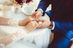 Mains des jeunes mariés avec des anneaux Photo stock