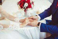 Mains des jeunes mariés avec des anneaux Images libres de droits