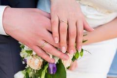 Mains des jeunes mariés avec des anneaux sur le bouquet de mariage Photographie stock