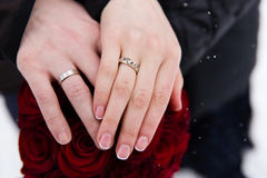 Mains des jeunes mariés avec des anneaux sur le bouquet de mariage Photo stock