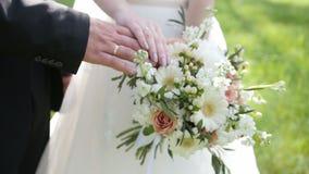 Mains des jeunes mariés avec les anneaux de mariage et le bouquet coloré clips vidéos