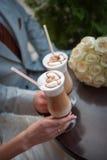 Mains des jeunes mariés Cappuccino ou café de latte avec le coeur Images stock