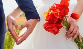 Mains des jeunes mariés dans une forme de coeur Le mariage, amour, entendent Photographie stock libre de droits