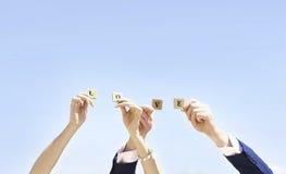 Mains des jeunes mariés gardant l'AMOUR de lettres Femme et amour d'homme Image stock