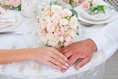Mains des nouveaux mariés avec des anneaux sur les doigts se trouvant sur la table sur le fond du bouquet de mariage photographie stock libre de droits