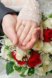 Mains des nouveaux mariés avec des boucles Photographie stock libre de droits