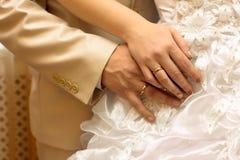 Mains des nouveaux mariés avec des boucles Photos stock