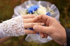 Mains des nouveaux mariés avec des boucles Images stock