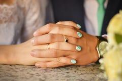 Mains des nouveaux mariés avec des boucles Image stock