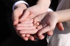 Mains des nouveaux mariés avec des boucles de mariage Photographie stock libre de droits