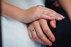 Mains des nouveaux mariés dans l'amour avec des anneaux d'or au mariage Image stock