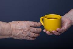 Mains des personnes âgées et des jeunes femmes sur le fond noir Images libres de droits