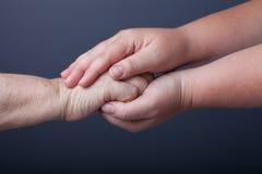 Mains des personnes âgées et des jeunes femmes sur le fond noir Photos stock