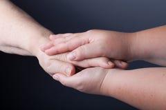 Mains des personnes âgées et des jeunes femmes sur le fond noir Image libre de droits