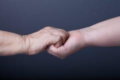 Mains des personnes âgées et des jeunes femmes sur le fond noir Photographie stock libre de droits