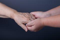 Mains des personnes âgées et des jeunes femmes sur le fond noir Photo libre de droits