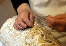 mains des personnes âgées tout en brodant une dentelle avec l'oreiller de dentelle Photo libre de droits