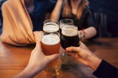 Mains des personnes tenant la bière et l'encourageant dans le bar de brasserie Les gens Photos libres de droits