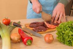 Mains des tranches d'une coupe de boucher de viande crue outre d'une grande échine pour le tournedos Images stock