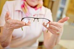 Mains des verres de offre d'opticien photos stock