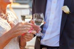 Mains des verres de tintement de jeunes mariés avec le champagne Photos stock