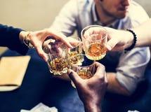 Mains diverses faisant tinter des verres d'alcool images stock