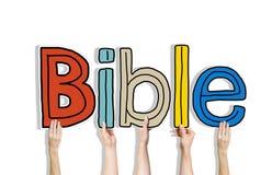 Mains diverses tenant la bible de Word Photographie stock