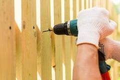 Mains du charpentier tenant le tournevis électrique dans le travail Photographie stock libre de droits