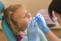 Mains du dentiste pédiatrique méconnaissable faisant la procédure d'examen pour la petite fille mignonne de sourire s'asseyant su photo libre de droits