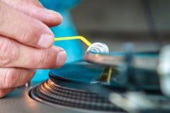 Mains du DJ mettant un disque vinyle dessus photos stock