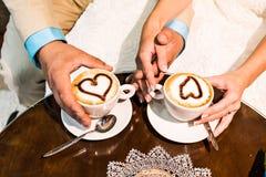 Mains du marié et de la jeune mariée avec des tasses de café Images stock