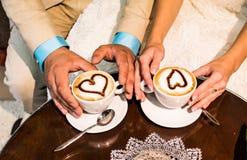 Mains du marié et de la jeune mariée avec des tasses de café Photo libre de droits