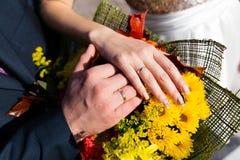 Mains du marié et de la jeune mariée sur le bouquet de mariage Image libre de droits