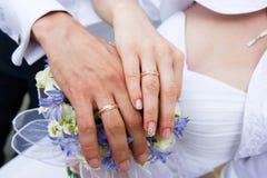 Mains du marié et de la jeune mariée sur le bouquet de mariage Image stock