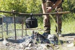 Mains du randonneur masculin faisant cuire sur le feu de camp dans la forêt d'été image libre de droits