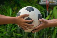 Mains du ` s d'enfant tenant le vieux football photo libre de droits