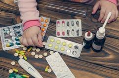 Mains du ` s d'enfants avec des médecines sur une table en bois Un petit enfant a laissé aux jeux sans surveillance les drogues d photographie stock