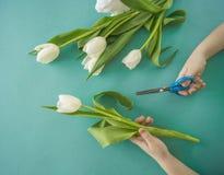 Mains du ` s d'enfants avec un bouquet de vue supérieure de tulipes Fond pour une carte d'invitation ou une félicitation La fille Photographie stock libre de droits